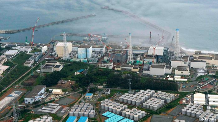 An aerial view shows Tokyo Electric Power Co. (TEPCO)'s tsunami-crippled Fukushima Daiichi nuclear power plant and its contaminated water storage tanks (bottom) in Fukushima, in this file photo taken by Kyodo August 20, 2013. Highly radioactive water overflowed barriers into Japan's Fukushima Daiichi nuclear power plant, its operating utility said on October 21, 2013, after it underestimated how much rain would fall at the plant and failed to pump it out quickly enough. After heavy rain on October 20, water with high levels of radioactive strontium overflowed containment areas built around some 1,000 tanks storing tonnes of radioactive water at the plant, Tepco said. Mandatory Credit. REUTERS/Kyodo/Files (JAPAN - Tags: DISASTER ENVIRONMENT POLITICS ENERGY) ATTENTION EDITORS - THIS IMAGE WAS PROVIDED BY A THIRD PARTY. FOR EDITORIAL USE ONLY. NOT FOR SALE FOR MARKETING OR ADVERTISING CAMPAIGNS. THIS PICTURE IS DISTRIBUTED EXACTLY AS RECEIVED BY REUTERS, AS A SERVICE TO CLIENTS. MANDATORY CREDIT. JAPAN OUT. NO COMMERCIAL OR EDITORIAL SALES IN JAPAN. YES