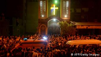 Ambulances drive through the crowd in front of the Virgin Mary Coptic Christian church in Cairo after gunmen on a motorbike shot dead three people late on October 20, 2013, including an eight-year-old girl, in a shooting attack on a group standing outside the church in the Egyptian capital's Al-Warak neighbourhood following a wedding ceremony. A health ministry official confirmed three people had been killed but said 12 people had in fact been wounded in the first such assault targeting Christians in Cairo since the military coup that ousted Islamist president Mohamed Morsi on July 3. AFP PHOTO / STR (Photo credit should read -/AFP/Getty Images)