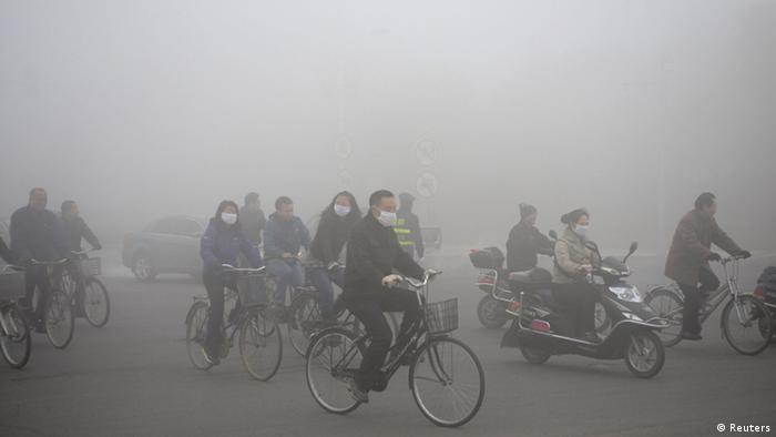 People ride along a street on a smoggy day in Daqing, Heilongjiang province, October 21, 2013. The highest red alert was issued for heavy smog in several cities in Heilongjiang province on Monday, according to Xinhua News Agency. The second day of heavy smog with a PM 2.5 index has forced the closure of schools and highways, exceeding 500 micrograms per cubic meter on Monday morning in downtown Harbin, the provincial capital. REUTERS/Stringer (CHINA - Tags: ENVIRONMENT SOCIETY) CHINA OUT. NO COMMERCIAL OR EDITORIAL SALES IN CHINA