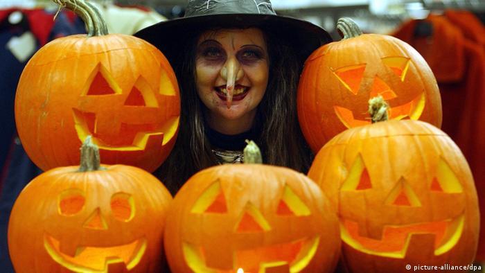 Eine als Hexe verkleidete Mitarbeiterin eines Hamburger Supermarktes posiert am 31.10.2003 mit Halloween-Kürbissen. Die menschliche Belegschaft hatte frei, dafür sprangen für einen Tag Hexen, Vampire und andere Schauergestalten ein. Zum Halloween-Fest war der Einkaufsmarkt fest in der Hand von - freundlich gesinnten - Monstern. Beim Betreten des Markts wurde klar, dass der Einkauf eine gehörige Portion Mut verlangen würde. Bereits am Eingang mussten sich die Kunden durch ein abgedunkeltes Gruselkabinett mit einem dichten Gewirr aus Spinnweben den Weg bahnen. Im Verkaufsraum erlebten sie eine Begrüßung durch einen Teufel. Nach Beratung durch die Hexen durften sie ihre Einkäufe schließlich beim lauernden Vampir an der Kasse mit zitternden Händen bezahlen.