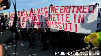 GettyImages 185481655 AGRIGENTO, ITALY - OCTOBER 21: A banner with the message 'the presence of the Eritrean regime offends the victims and endangers the survivors' is diplayed during the commemoration ceremony for the victims of the boat sinking disaster off the Lampedusa coast on October 21, 2013 in San Leone near Agrigento, Italy. Victims of the Lampedusa disaster, which killed more than 300 asylum seekers when the boat they were on sank have been buried in unknown vaults despite Italian Prime Minister Enrico Letta's promise to hold a state funeral for the dead. (Photo by Tullio M. Puglia/Getty Images)