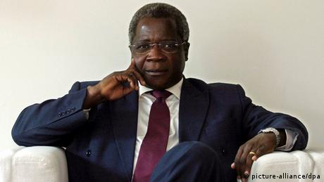 Dhlakama in a dark suit on a white sofa