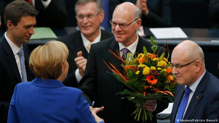 Norbert Lammert (C) reelected President of Germany's lower house of parliament, is presented flowers by German Chancellor and leader of the Christian Democratic Union (CDU) Angela Merkel, during the constitutional meeting of the Bundestag in Berlin October 22, 2013. REUTERS/Fabrizio Bensch (GERMANY - Tags: POLITICS)