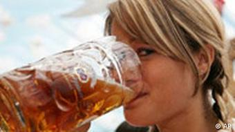 A blonde female drinks a large jug of beer
