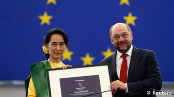 Myanmar pro-democracy leader Aung San Suu Kyi (L) holds her 1990 Sakharov Prize, besides European Parliament President Martin Schulz during an award ceremony in Strasbourg, October 22, 2013.