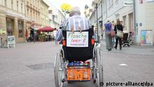 Ein älterer Herr fährt am 28.08.2013 in seinem Rollstuhl mit der Aufschrift «Flasche leer? Dankesehr!» durch die Fußgängerzone von Potsdam (Brandenburg). In den Städten sind immer häufiger Flaschensammler zu sehen, die sich mit dem Einsammeln von Pfandflaschen etwas Geld dazu verdienen wollen. Foto: Kay Nietfeld/dpa
