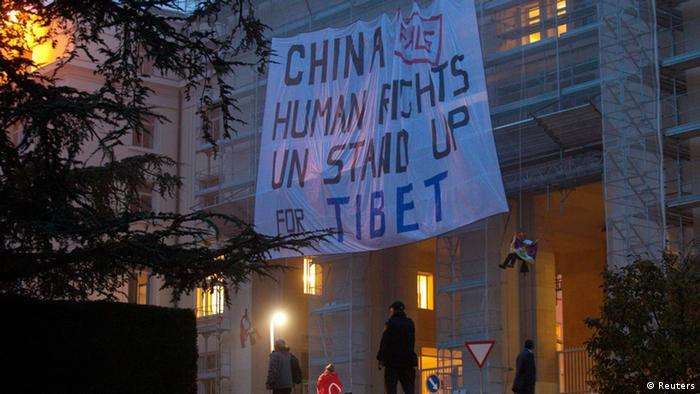 Members of the Students for a Free Tibet organisation display a banner on scaffolding in front of the European headquarters of the United Nations in Geneva October 22, 2013. The 17th session of the Human Rights Council's Universal Periodic Review (UPR) Working Group will be held in Geneva from October 21 to November 1, during which 15 states are scheduled to have their human rights records examined. China's review on its human rights situation is scheduled for Tuesday. REUTERS/Denis Balibouse (SWITZERLAND)
