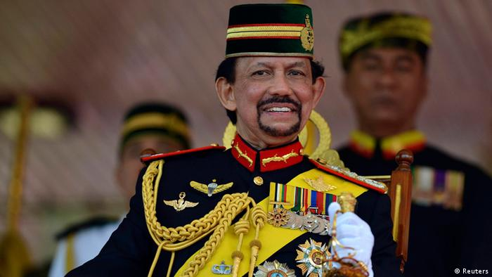 Brunei's Sultan Hassanal Bolkiah smiles as he sits on a stage in Bandar Seri Begawan, in this September 15, 2013 file photo. REUTERS/Ahim Rani/Files
