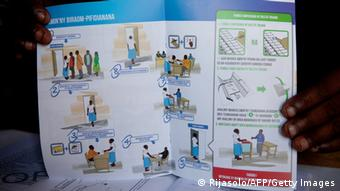 GettyImages 185550303 View of a pamphlet explaining people how to vote as Independent National Electoral Commission for Transition (CENI-T) members set up a polling station in Antananarivo on October 21, 2013 ahead of the elections on October 25, 2013. Absent from Friday's presidential election in Madagascar, the current country's strongman Andry Rajoelina and former President Marc Ravalomanana closely monitor the polls which are also followed by mysterious but generous donors, anxious to defend their local economic positions. The two main protagonists in the Malagasy crisis have their favorites among the 33 candidates. Marc Ravalomanana has dubbed the physician Jean Louis Robinson, while three other candidates come from the TGV, Rajoelina's party. AFP PHOTO / RIJASOLO (Photo credit should read RIJASOLO/AFP/Getty Images)