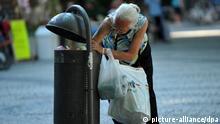 ARCHIV - Im Müllbehälter sucht eine ältere Frau am 08.07.2010 in der Schillerstraße in Weimar nach Pfandflaschen. Die Online-Plattform «pfandgeben.de» bietet die Möglichkeit, das Leergut, das sich mit der Zeit in privaten Küchen ansammelt, an Flaschensammler zu spenden. Längst gehen nicht mehr nur Wohnsitzlose auf Sammeltour, auch immer mehr Hartz-IV-Empfänger und Rentner versuchen so, ein paar Euro zusätzlich zu verdienen. Foto: Martin Schutt dpa (zu dpa/lbn «Einmal Flaschensammeln, bitte» vom 28.07.2011) +++(c) dpa - Bildfunk+++