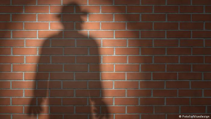 Тень человека на кирпичной стене