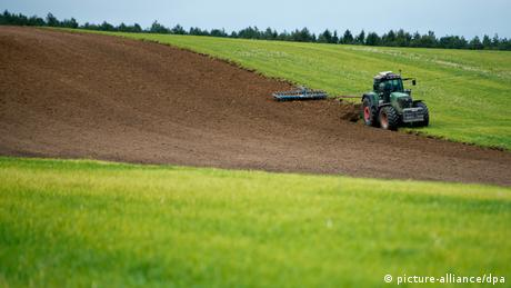 A tractor turning over soil in a green field