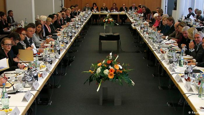 A long u-shaped table overflows with politicians in a crowded room.