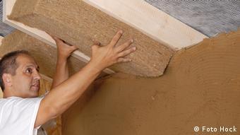 Mann dämmt eine Kellerdecke