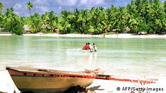 A traditional Micronesian canoe sits on the shore as people cross a lagoon on an atoll of Tarawa in the central Pacific's Kiribati. (Photo credit should read MICHAEL J. FIELD/AFP/Getty Images)