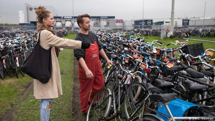 A woman stands beside a man and points to a bike (photo: Carl Nasman)