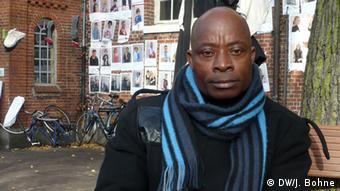 Porträt Asuquo Udo Bildbeschreibung: Der nigerianische Flüchtling Asuquo Udo sitzt auf einer Bank vor der Hamburger St. Pauli Kirche Bildunterschrift: Asuquo Udo hofft auf ein Bleiberecht in Hamburg Bild: DW/Julian Bohne Oktober 2013