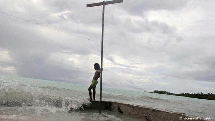 A young girl on the South Pacific island of Kiribati, watches the sea water during a king tide wash over a wall built by her family to protect their land from erosion by the encroaching sea. (Photo: EPA/Jeremy Sutton-Hibbert)