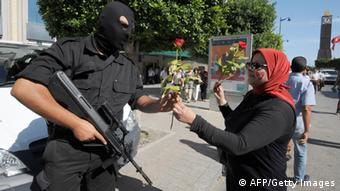 A Tunisian woman hands a rose to a riot policeman (FETHI BELAID/AFP/Getty Images)