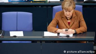 Merkel using her mobile phone in the Bundestag Photo: Maurizio Gambarini/dpa