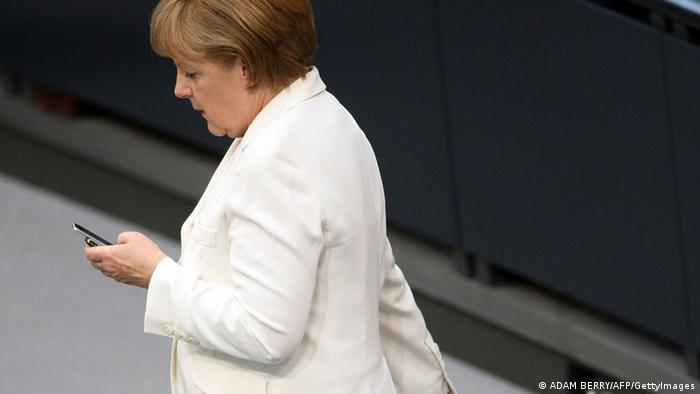 German Chancellor Angela Merkel looks at her mobile telephone as she arrives to address German lawmakers before they vote on the EU fiscal pact and permanent ESM bailout fund, at the lower Bundestag house of parliament in Berlin on June 29, 2012. The 620 members of the Bundestag will vote on the EU fiscal pact which commits Germany and its partners to more budgetary discipline and on the creation of the ESM, the permanent rescue fund which is to take over starting next month from the European Financial Stability Facility (EFSF). AFP PHOTO / ADAM BERRY (Photo credit should read ADAM BERRY/AFP/GettyImages)