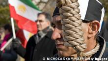 A protestor wears a noose as another waves an Iranian flag during a demonstration to demand the continued US protection of 3,500 members of Iran's oppostion People's Mojahedin of Iran (PMOI/MEK) at Camp Ashraf in Iraq's Diyala province, some 40 miles (65km) north of Baghdad, in Washington on December 5, 2008. Supporters of PMOI/MEK say the transfer of protection to the Iraqi government would put members at grave risk. AFP PHOTO/Nicholas KAMM (Photo credit should read NICHOLAS KAMM/AFP/Getty Images)