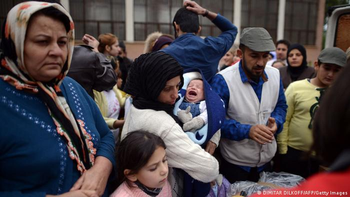 A Syrian woman holds her baby as she waits with other Syrians to receive food, clothes and blankets from the Bulgarian Red Cross at a refugee center in Sofia on October 3, 2013. Boris Cheshirkov, spokesman for the UN Refugee Agency in Bulgaria, warned this week about food shortages in the shelters. In an accommodation centre near Sofia, one blanket had to be shared between three people, he said. More than two million people have fled Syria since the war broke out there in 2011, mostly to neighbouring Lebanon, Turkey, Jordan and Iraq. AFP PHOTO / DIMITAR DILKOFF (Photo credit should read DIMITAR DILKOFF/AFP/Getty Images)