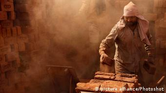 A laborer loads bricks onto his handcart in a brick kiln at Malpora village of Anantnag district, about 60 km south of Srinagar, the summer capital of Indian-controlled Kashmir, on Oct. 17, 2012. (Photo: dpa)