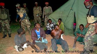 A picture taken on October 17, 2013 shows prisoners belonging to former Mozambican rebel movement Renamo sitting on the ground with government soldiers guarding them in Gorongosa. Mozambique ex-rebel group Renamo has declared on October 21, 2013 the end of a peace deal signed 21 years ago after the army seized its military base. A spokesman for Renamo, Mozambique's main opposition party, accused the army of trying to kill the group's president Afonso Dhlakama, and said the deal that ended the country's 16-year civil war was over. AFP PHOTO / MARIA CELESTE MAC' ARTHUR (Photo credit should read MARIA CELESTE MAC' ARTHUR/AFP/Getty Images)