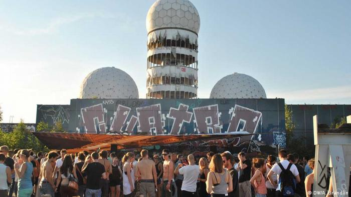 An open-air festival on the former soy station with the radar domes in the background and young people dancing and chilling in the foreground Photo: Anne-Sophie Brändlin, am 27.08.2012 in Berlin