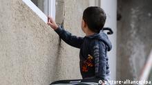 A boy standing at a window Photo: Daniel Bockwoldt/dpa