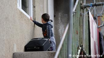 Ein Junge mit einem Koffer in der Hand schaut in ein Fenster einer Asylunterkunft in Tübingen, Foto von Daniel Bockwoldt/dpa