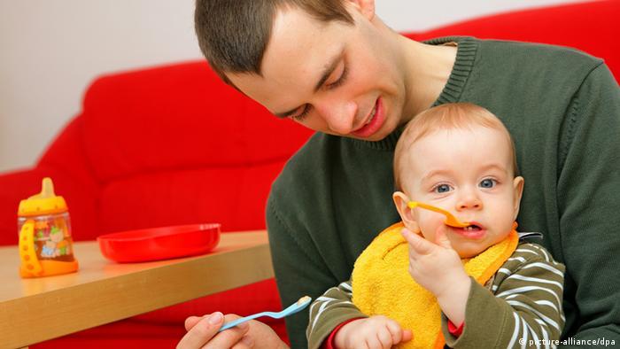 Отец кормит ребенка