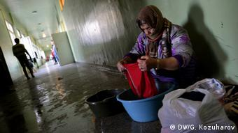 A woman washes clothes in a bowl in a Syrian refugee camp in Bulgaria. (Photo: Georgi Kozuharov)