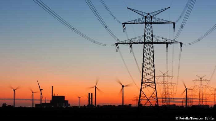 Strommast bei Sonnenuntergang mit Windrädern und Kernkraftwerk (Foto: Fotolia)