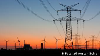 Strommast bei Sonnenuntergang mit Windrädern und Kernkraftwerk