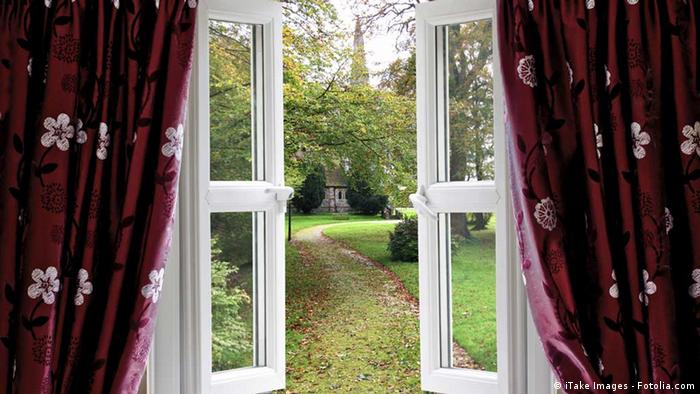 An open window with curtains and a garden in te background