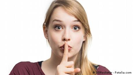 A woman puts her index finger over her mouth, indicating a sssssh, silence is wanted