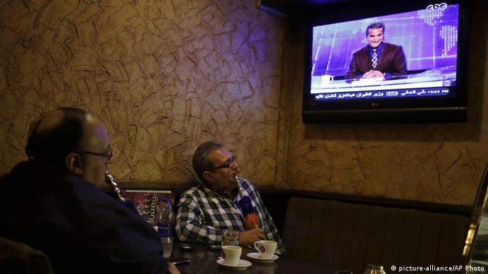 Egyptians watch the weekly program of Bassem Youssef, the man known as ¿Egypt¿s Jon Stewart,¿ at a coffee shop in Cairo, Egypt, Friday, Oct. 25, 2013. Egypt¿s most popular TV satirist, famed for mercilessly skewering the former Islamist president on his weekly program, dove headfirst back into stormy politics Friday after four months off the air amid the turmoil surrounding the country¿s coup. His new target for mockery: the over-the-top pro-military fervor sweeping Egyptians. Youssef returned to the air in a radically different nation, where satirizing the leadership is a far trickier task. (AP Photo/Khalil Hamra)