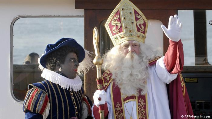 A caucasian in blackface and wearing the clothes of a jester stands next to the red-and-white berobed figure of a white-bearded caucasian Saint Nikolaus figure. Photo: Dirk Waem