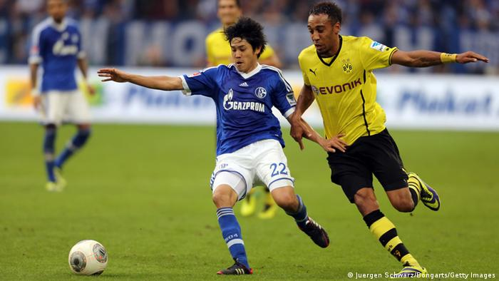 Atsuto Uchida of Schalke (L) and Pierre-Emerick Aubameyang of Dortmund fight for the ball during the Bundesliga match between Schalke 04 and Borussia Dortmund at Veltins-Arena on October 26. Photo: Getty