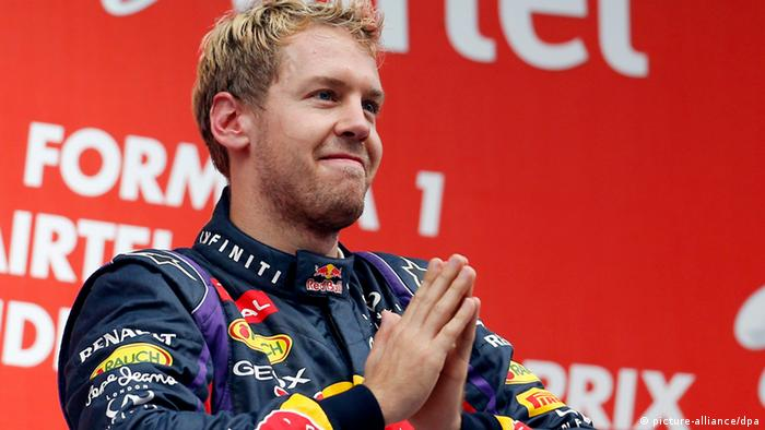 epa03926575 German Formula One driver Sebastian Vettel of Red Bull Racing celebrates on the podium after winning the 4th consecutive Formula One Championship title at the Buddh International Circuit on the outskirts of New Delhi, India, 27 October 2013. EPA/VALDRIN XHEMAJ