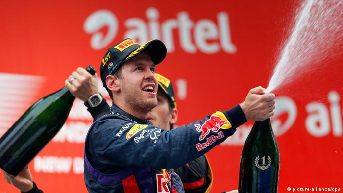 epa03926553 German Formula One driver Sebastian Vettel of Red Bull Racing celebrates on the podium after winning the 4th consecutive Formula One Championship title at the Buddh International Circuit on the outskirts of New Delhi, India, 27 October 2013. EPA/VALDRIN XHEMAJ +++(c) dpa - Bildfunk+++