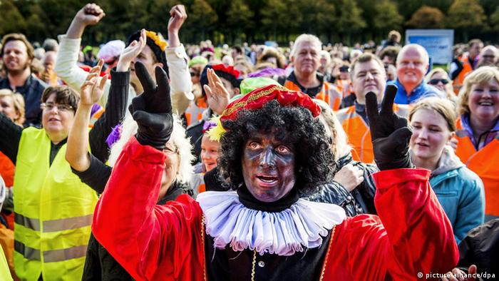 Hundreds of brightly-dressed protestors, some wearing wigs and in blackface, march down the street. Photo: Koen van Weel