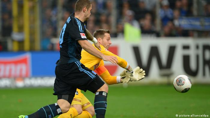 Pierre-Michel Lasogga gets set to capitalize on Freiburg goalkeeper Oliver Baumann's ill-advised rush out of his area. Photo: dpa