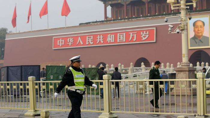 A policeman walks past in front of the giant portrait of the late Chinese Chairman Mao Zedong as other policemen clean up after a car accident at the Tiananmen Square in Beijing, October 28, 2013. Chinese police on Monday evacuated Beijing's Tiananmen Square, the site of 1989 pro-democracy protests bloodily suppressed by the government, following a fire after a car ran into a crowd, a Reuters witness and state media said. REUTERS/Jason Lee