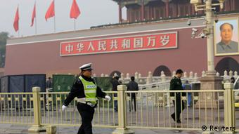 A policeman walks past in front of the giant portrait of the late Chinese Chairman Mao Zedong as other policemen clean up after a car accident at the Tiananmen Square in Beijing, October 28, 2013. Chinese police on Monday evacuated Beijing's Tiananmen Square, the site of 1989 pro-democracy protests bloodily suppressed by the government, following a fire after a car ran into a crowd, a Reuters witness and state media said. REUTERS/Jason Lee (CHINA - Tags: SOCIETY POLITICS)