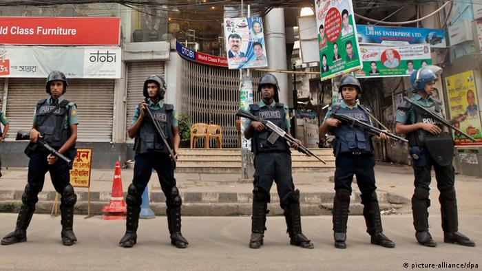 Bangladeshi police officials stand guard on a street during a general strike in Dhaka, Bangladesh, Monday, Oct. 28, 2013. At least 13 people have died since Friday in violence as the government of Prime Minister Sheikh Hasina and an 18-party alliance led by opposition leader Khaleda Zia disagree over forming a caretaker government. The opposition began the three-day general strike on Sunday to force the government to quit and form an independent government to oversee an election due by early next year. (AP Photo/A.M. Ahad)