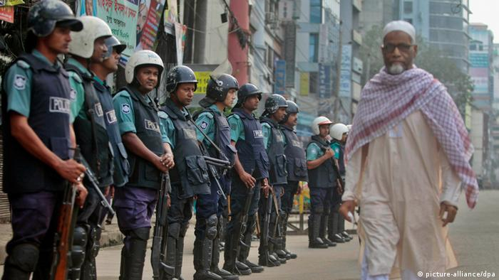 Bangladeshi riot policemen stand guard on a street outside the office of the main opposition Bangladesh Nationalist Party (BNP) as a man walks past them during a general strike in Dhaka, Bangladesh, Monday, Oct. 28, 2013. At least 13 people have died since Friday in violence as the government of Prime Minister Sheikh Hasina and an 18-party alliance led by opposition leader Khaleda Zia disagree over forming a caretaker government. The opposition began the three-day general strike on Sunday to force the government to quit and form an independent government to oversee an election due by early next year. (AP Photo/A.M. Ahad)