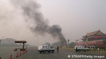 Police cars block off the roads leading into Tiananmen Square as smoke rises into the air after a vehicle crashed in front of Tiananmen Gate in Beijing on October 28, 2013. (Photo: AFP)